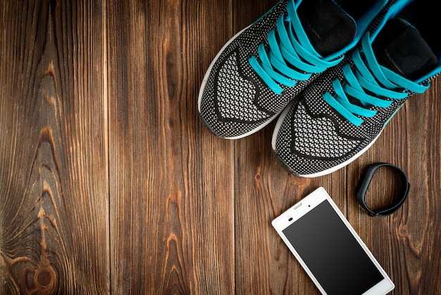 Fitness tracker and sneakers on wooden table.