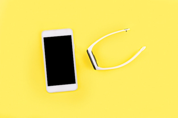 Fitness tracker with white bracelet and smartphone on the yellow background.