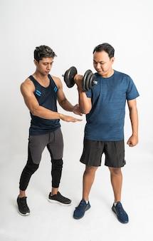 フィットネストレーナーは、上腕二頭筋のエクササイズのためにダンベルを持ち上げる男性に手を添えて正しい動きをさせる