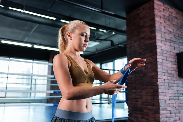 Fitness trainer. blonde-haired beautiful fitness trainer rolling her hands in wrist wraps while standing in gym