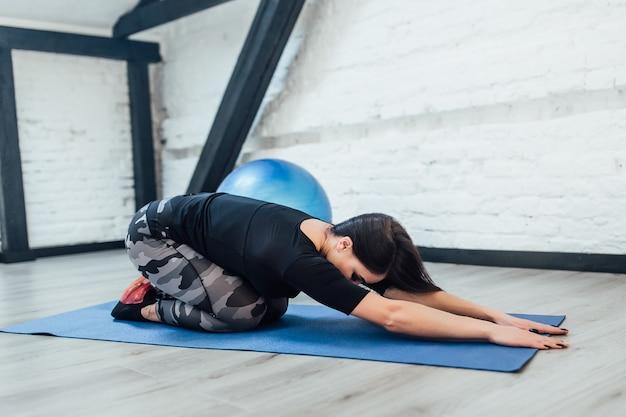 L'istruttore di fitness ha un momento di pilates nella stanza bianca della palestra