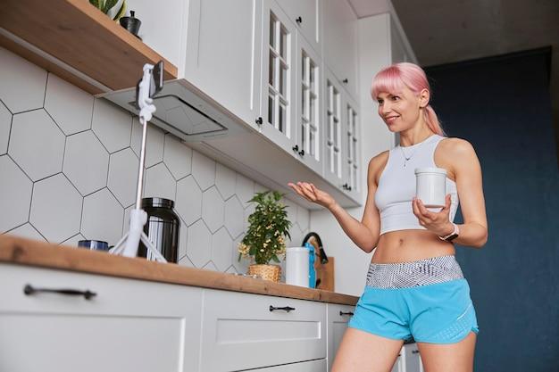 フィットネストレーナーは、キッチンで新しいビデオを撮影する栄養補助食品の瓶を保持しています