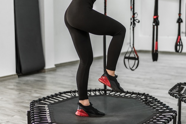 Фитнес-тренер в черных леггинсах прыгает в современном тренажерном зале