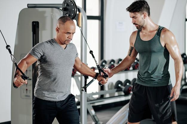Тренер по фитнесу смотрит на клиента, выполняющего упражнения в тренажере с кабельным кроссовером для верхней части груди и рук