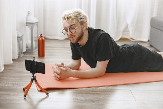 스트레칭을하는 피트니스 트레이너 또는 비디오 블로거. 남자는 집에서 스마트 폰 카메라로 자신을 촬영하고 있습니다.