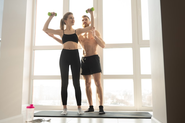 Fitness trainer show exercise for shoulders with dumbbells to sportswoman. blonde woman wear sportswear. man with naked torso. concept of sport activity at home. interior of spacious sunny apartment