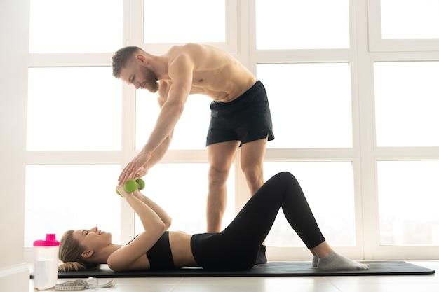피트니스 트레이너는 피트니스 매트에 있는 스포츠우먼에게 아령으로 운동을 보여줍니다. 금발의 여자는 운동복을 입는다. 벌거 벗은 몸통을 가진 남자. 집에서 스포츠 활동의 개념입니다. 넓은 햇볕이 잘 드는 아파트의 인테리어