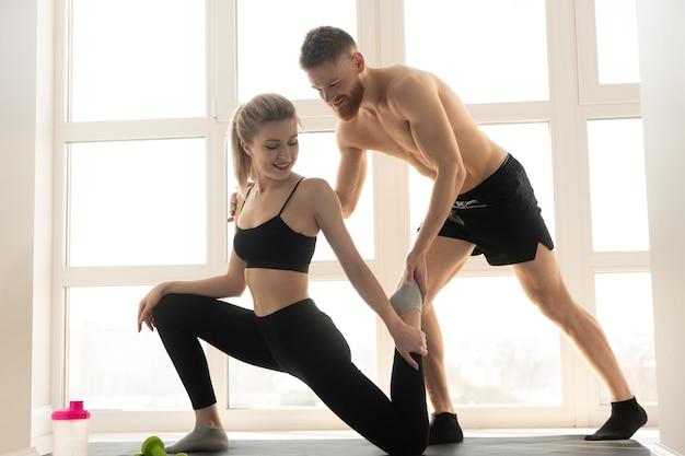 피트니스 매트에 운동가에게 스트레칭을 보여주는 피트니스 트레이너. 금발의 여자는 운동복을 입는다. 벌거 벗은 몸통을 가진 수염 난 남자. 집에서 스포츠 활동의 개념입니다. 넓은 햇볕이 잘 드는 아파트의 인테리어