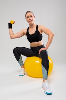 Fitness trainer shows exercises for the body on a gray