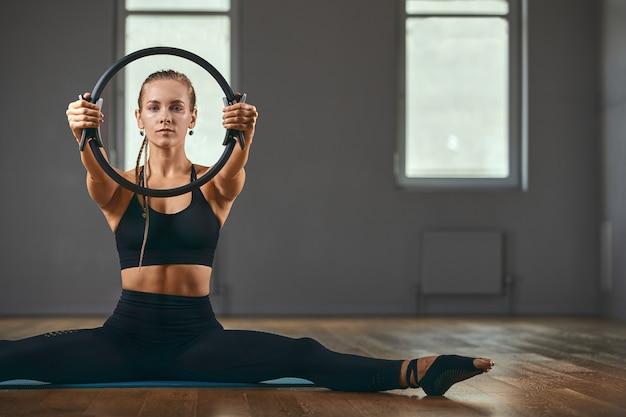フィットネストレーナーは、ラバーエキスパンダーを使用してエクササイズを示します。美しい体へのモチベーション。フィットネスバナー、コピースペース。