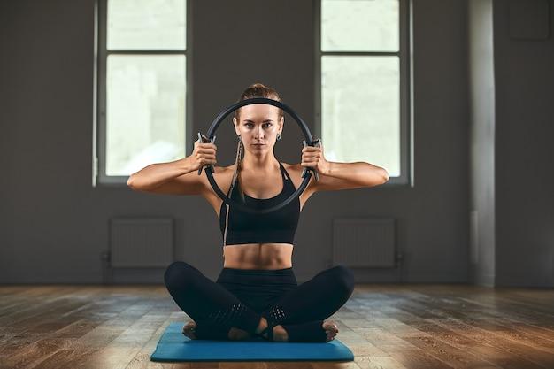 フィットネストレーナーは、ラバーエキスパンダーを使ったエクササイズを披露します。美しい体へのモチベーション。フィットネスバナー、コピースペース。