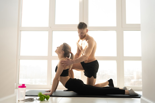 Fitness trainer training sportswoman on fitness mat. young blonde woman wear sportswear. bearded man with naked torso. concept of sport activity at home. interior of modern spacious sunny apartment