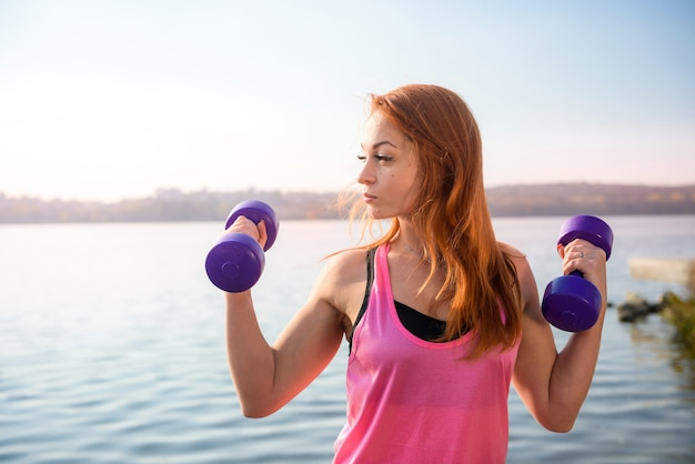 Fitness training - beautiful young woman working exercise  with dumbbells, as a part of her lifestyle.