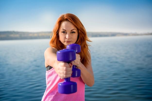 체력 훈련-아름 다운 젊은 여자 작업 아령 운동
