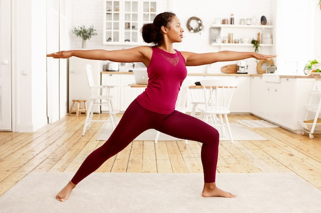 Fitness, training, health and wellness concept. side view of athletic young afro american housewife in stylish sportswear practicing yoga in the morning, doing warrior 2 pose on mat in kitchen