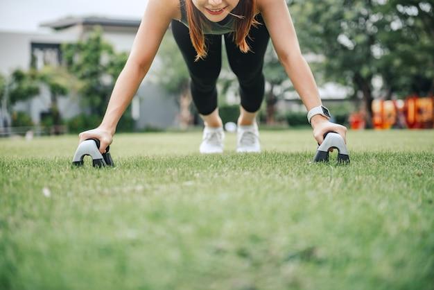 Тренировка фитнеса на открытом воздухе, женщина делает отжимания в парке.