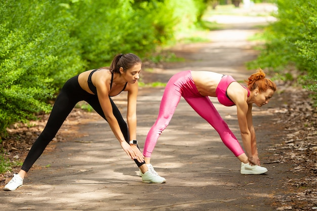 Fitness. two female runners stretching legs outdoors in park in summer