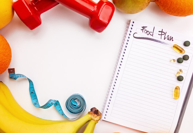 Fitness and weight loss concept, dumbbells, white notebook, fruit, tape measure, vitamins and supplements on white background ,mockup copy past, top view