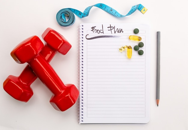 Fitness and weight loss concept, dumbbells, white notebook, tape measure, vitamins and supplements on white background, top view