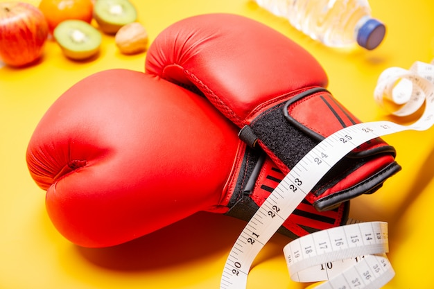 Fitness. weight loss or exercise concept. boxing gloves, healthy food and measure tape