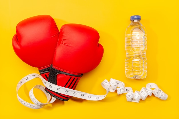 Fitness, weight loss or exercise concept. boxing gloves, mineral water and measure tape isolated