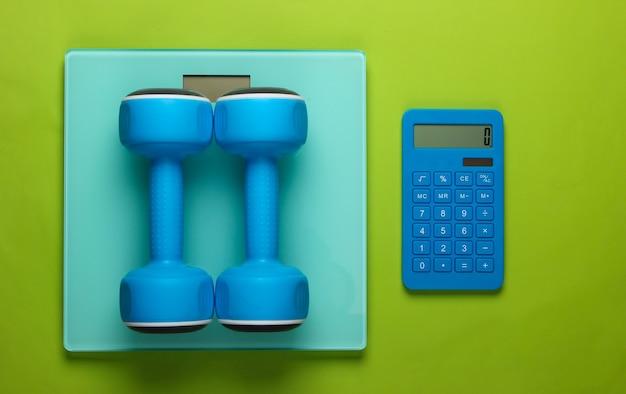 피트니스, 체중 감량 정물. 칼로리 계산. 계산기, 아령 및 비늘 녹색. 미니멀리즘. 플랫 레이