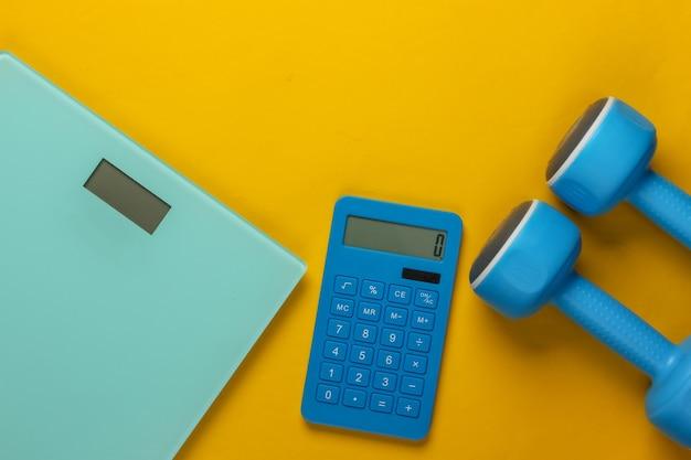 Фитнес, потеря веса натюрморт. подсчет калорий. калькулятор, гантели и весы на желтом. минимализм.