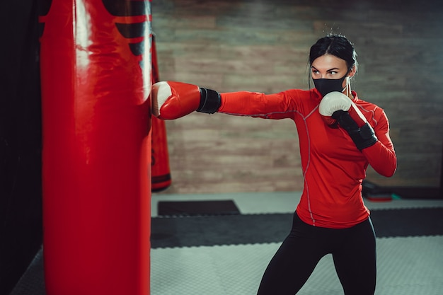 Fitness woman boxing with face mask