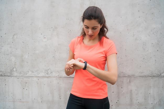 フィットネス女性がスマートな時計で時間をチェックします。