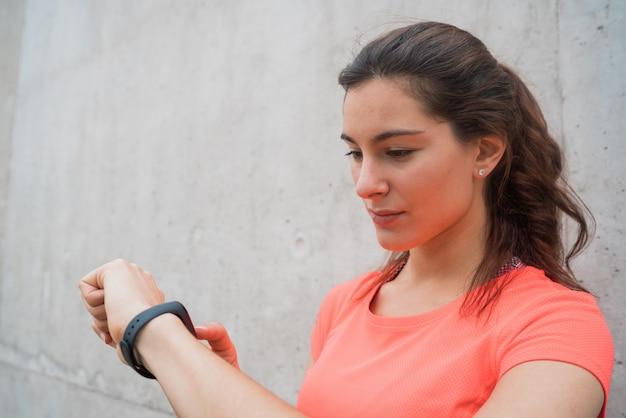 スマートな時計で時間をチェックするフィットネス女性