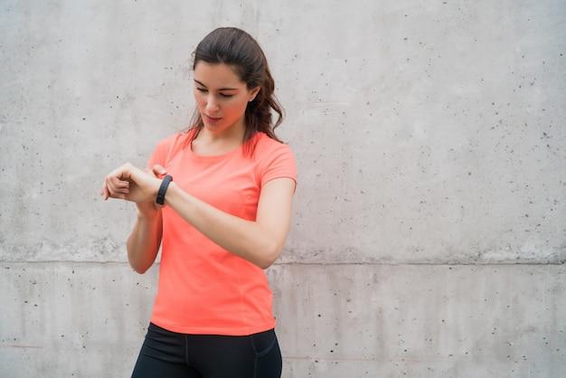 フィットネス女性がスマートな時計の時間をチェックします。