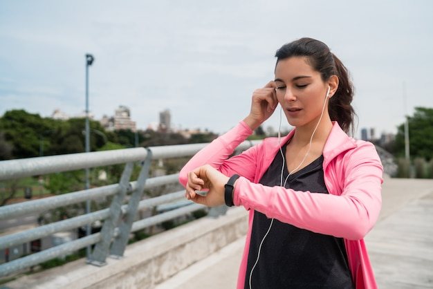 Fitness woman checking time on smart watch.