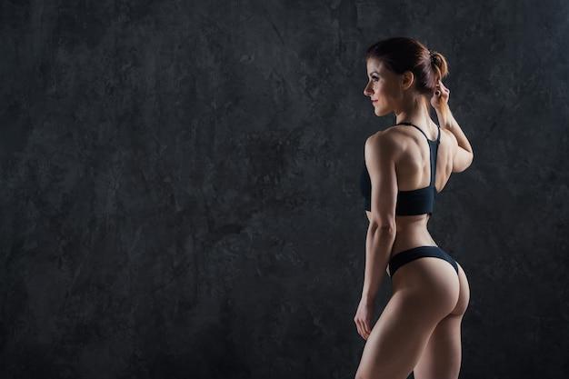 Fitness woman on a dark wall