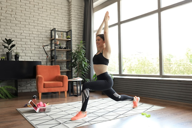 Fitness woman doing forward lunge exercises and watching online tutorials on laptop, training in living room. stay at home activities.