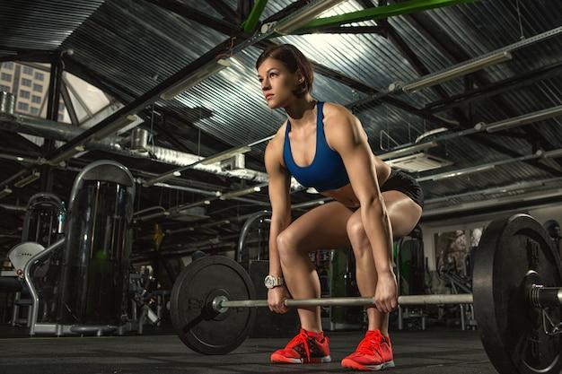 ジムでバーベルで重い重量挙げトレーニングを行うフィットネス女性