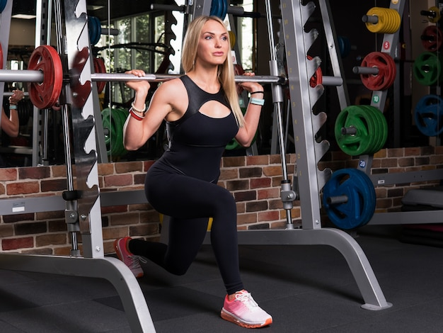 Fitness woman doing lunge squats on simulator in gym