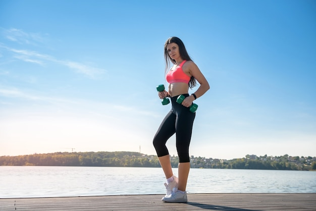 湖の小さな重みで朝の運動をしているフィットネス女性