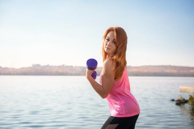 Женщина фитнеса делает утреннюю тренировку с небольшими весами озера