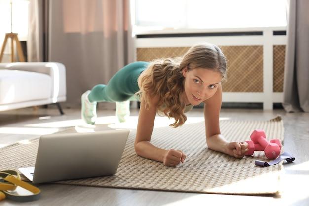 Женщина фитнеса делает планку и смотрит онлайн-уроки на ноутбуке, тренируется в гостиной. оставайтесь дома.