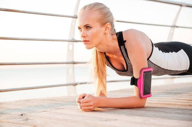 Женщина фитнеса делает упражнения йоги планки на открытом воздухе на пирсе пляжа