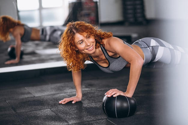 Fitness woman doing push-ups at the gym