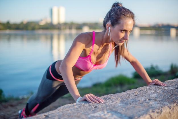 プッシュアップを行うフィットネス女性屋外トレーニングトレーニング夏の夜の側面図コンセプトスポーツ健康的なライフスタイル。