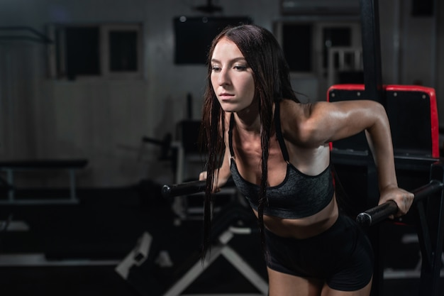 Fitness woman doing push-ups on uneven bars in crossfit gym,