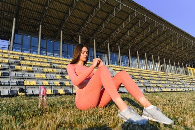 Женщина фитнеса делает приседания в разработке стадиона. спортивная девушка упражнениями брюшного пресса, открытый