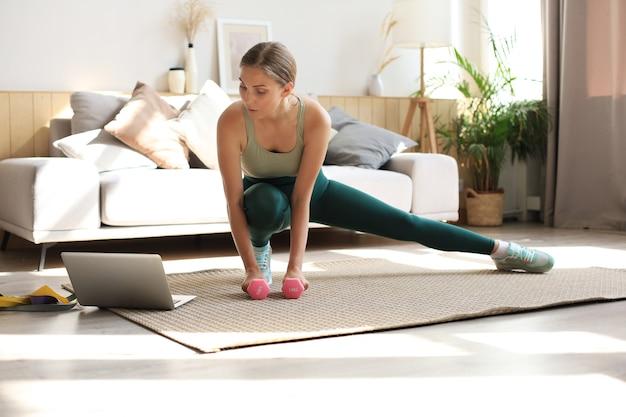 Женщина фитнеса делает спортивные упражнения и смотрит онлайн-уроки на ноутбуке, тренируется в гостиной. оставайтесь дома.
