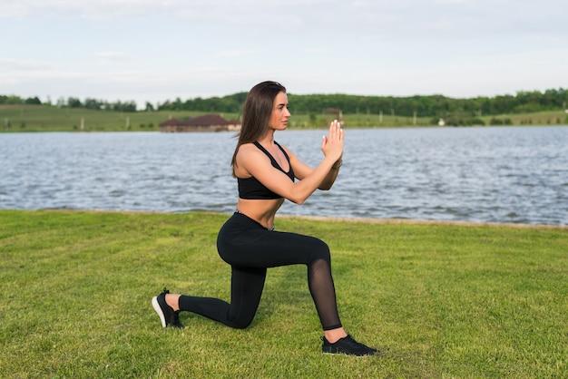 Женщина фитнеса делая приседания в парке. тренировка на свежем воздухе на свежем воздухе. концепция спорта здорового образа жизни.