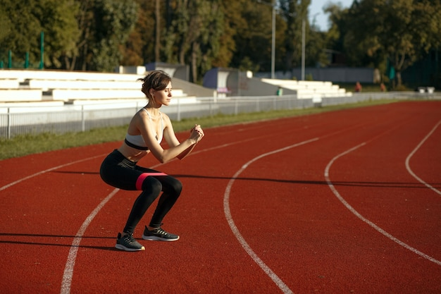 Fitness woman doing  squats with a resistance band at the stadium. empty space