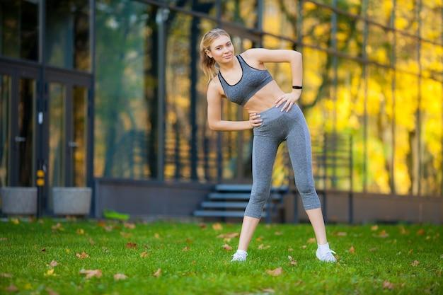 フィットネス。公園でストレッチ運動をしている女性。