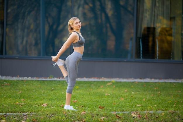 Фитнес. женщина делает упражнения на растяжку в парке.
