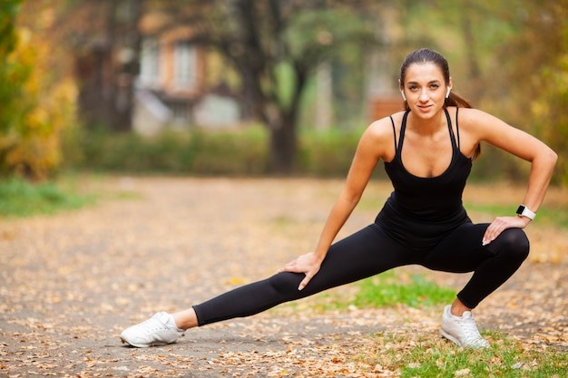 Fitness, woman doing stretching exercise on park